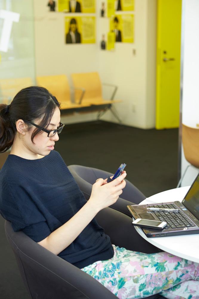 社内のオープンスペースにて。会社貸与のスマートフォンで、社内外どこにいても予定管理がスムーズに。